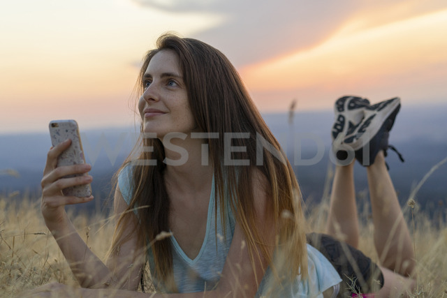 Smiling young woman with cell phone lying in grass during sunset - AFVF01365