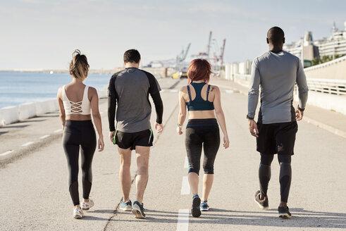 Group of sportspeople walking, rear view - JNDF00025