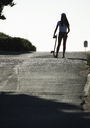 Young woman standing on a road holding a skateboard. - MINF06627