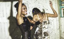 Two women wearing cocktail dresses at a party dancing in a shower of glitter confetti. - MINF06666