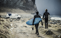 Two surfers wearing wetsuits and carrying surfboards walking towards a van. - MINF06672