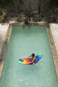 High angle shot of a boy sitting on a pool raft, watched by a man at the edge of swimming pool. - MINF06681