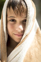 Close up of a boy wrapped in a towel smiling into shot. - MINF06687