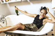 Young woman sitting in a bath holding a champagne bottle. - MINF06723