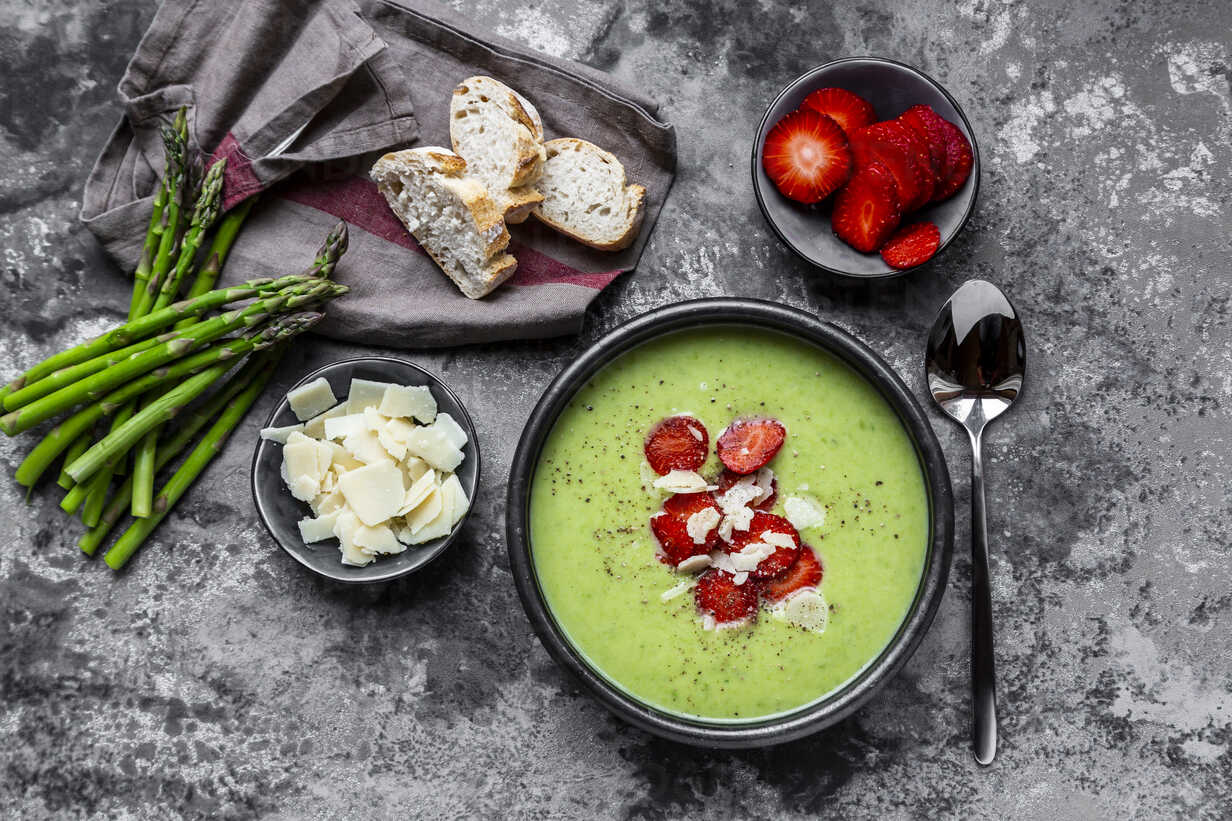 Green asparagus cream soup with strawberry, parmesan and baguette - SARF03878 - Sandra Roesch/Westend61