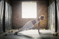 A blonde woman, in a white crop top and leggings, standing on a yoga mat surrounded by candles, doing yoga, her arm raised. - MINF06776