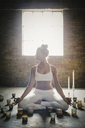 A blonde woman in a white crop top and leggings, sitting on the floor surrounded by candles, doing yoga. - MINF06779