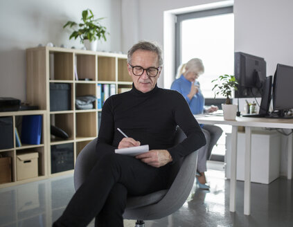 Senior man sitting in office taking notes with colleague working behind him - AWF00180