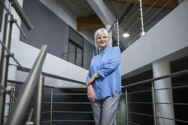 Smiling senior businesswoman standing on office hallway - AWF00192