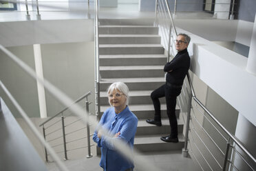 Two senior colleagues standing on office stairs - AWF00195