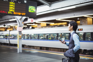 Businessman wearing blue shirt and vest standing on train station platform, holding mobile phone. - MINF06800