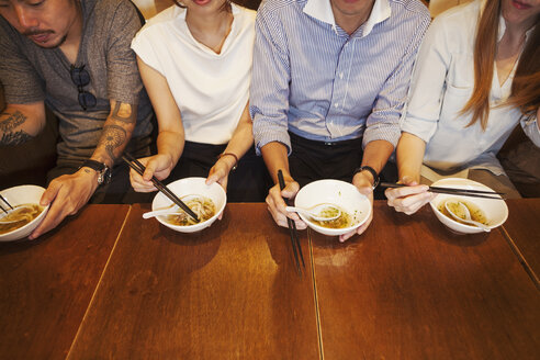 High angle close up of four people sitting sidy by side at a table in a restaurant, eating from bowls using chopsticks. - MINF06869