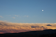 A full moon rises over fiery clouds at sunset. - AURF00028