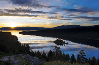 A magnificent sunrise over Emerald Bay with clouds reflecting in the calm water in Lake Tahoe, CA. - AURF00031