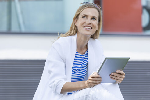 Smiling blond businesswoman using tablet - TCF05540