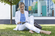 Blond businesswoman using tablet sitting on meadow - TCF05543