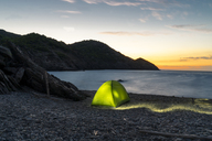Spain, Catalonia, Costa Brava, green tent at stony beach in the evening - AFVF01374