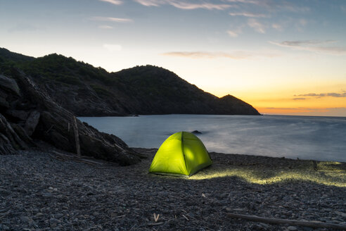 Spain, Catalonia, Costa Brava, green tent at stony beach in the evening - AFVF01374