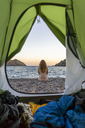 Spain, Catalonia, Costa Brava, naked woman sitting at beach, view from tent - AFVF01377