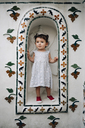 Thailand, Bangkok, Wat Arun, cute baby girl standing in a niche of the temple - GEM02252