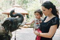 Thailand, Chiang Mai, Woman and child admiring the statue of an elephant at the Wat Pha Lat Buddhist temple - GEMF02272