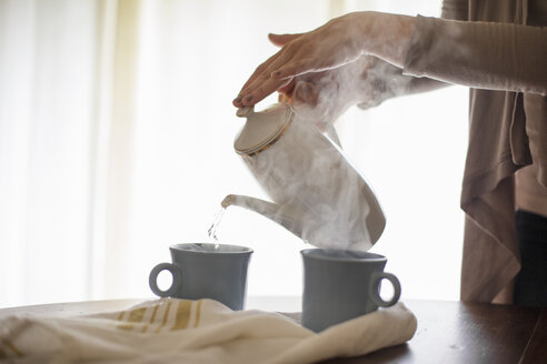 Close up of a woman pouring hot water from a coffee pot into a mug. - MINF06940