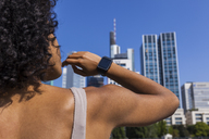 Germany, Frankfurt, back view of  young woman wearing smartwatch - TCF05573