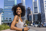 Germany, Frankfurt, portrait of smiling young woman with curly hair in the city - TCF05579