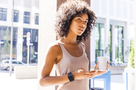 Portrait of pensive young woman with coffee to go and cell phone - TCF05594
