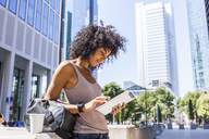 Germany, Frankfurt, young woman with travelling bag and coffee to go using digital tablet in the city - TCF05597