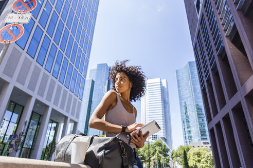 Germany, Frankfurt, young woman with travelling bag, tablet and coffee to go in the city - TCF05600