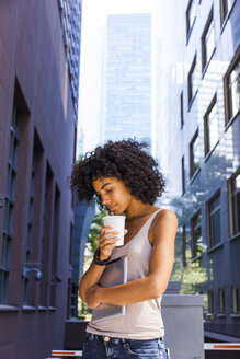Germany, Frankfurt, young woman with tablet and coffee to go in the city - TCF05606