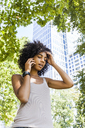 Germany, Frankfurt, portrait of young woman on the phone in front of skyscraper - TCF05612