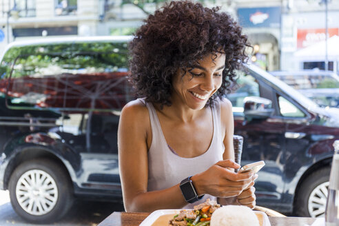 Portrait of smiling young woman with  sitting at pavement restarant looking at cell phone - TCF05615