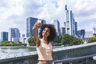 Germany, Frankfurt, portrait of content young woman with curly hair taking selfie in front of skyline - TCF05624