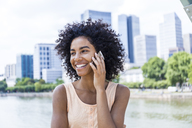 Germany, Frankfurt, portrait of smiling young woman with curly hair on the phone - TCF05630