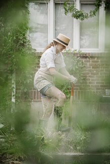 A woman in a wide brimmed straw hat working in a garden, digging. - MINF07166