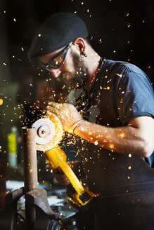 A man using a buzz saw to cut into a metal pipe. - MINF07295