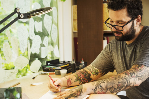 Bearded man with tattoos on his arms, sitting at a desk, drawing. - MINF07427