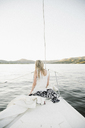 Blond teenage girl sitting on sail boat. - MINF07448