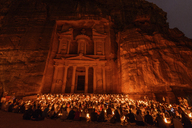 Exterior view of the rock-cut architecture of Al Khazneh or The Treasury at Petra, Jordan with large group of people sitting on the ground at night. - MINF07496