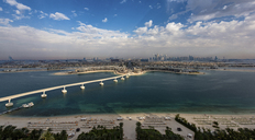 Cityscape of Dubai, United Arab Emirates, with bridge from  island across the Persian Gulf in the foreground. - MINF07520