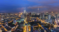 Cityscape of Kuala Lumpur, Malaysia at dusk, with illuminated Petronas Towers and communication tower in the distance. - MINF07595