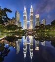Illuminated Petronas Towers building in Kuala Lumpur, Malaysia at dusk. Reflection in lake. - MINF07598