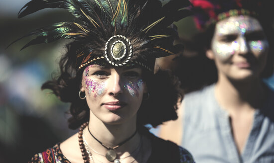 Young woman at a summer music festival face painted, wearing feather headdress, looking at camera. - MINF07622