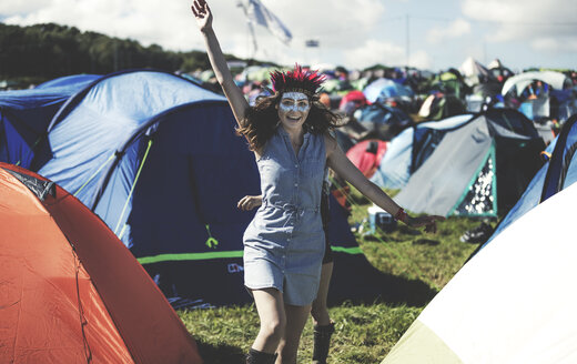 Young woman at a summer music festival face painted, wearing feather headdress, standing near the campsite surrounded by tents, arm raised, smiling. - MINF07625