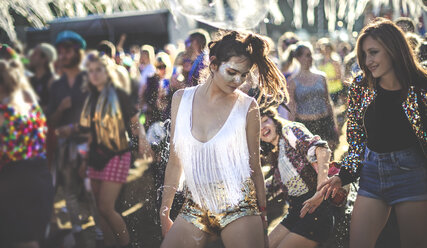 Young woman at a summer music festival wearing golden sequinned hot pants, dancing among the crowd. - MINF07631