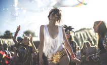 Young woman at a summer music festival wearing golden sequinned hot pants, dancing among the crowd. - MINF07634