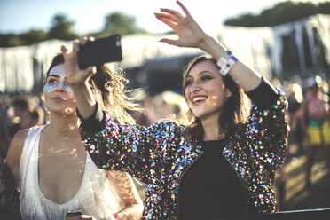Young smiling woman at a summer music festival wearing multi-coloured sequinned jacket, taking picture with smartphone. - MINF07640