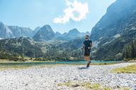 Austria, Tyrol, Man hiking at Seebensee Lake - DIGF04735